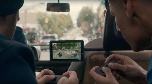 Zwei Männer sitzen vor einem Tablet und halten kleine Controller in den Händen.