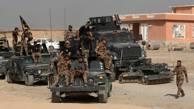 Soldaten der irakischen Armee sitzen auf ihren Geländewagen.