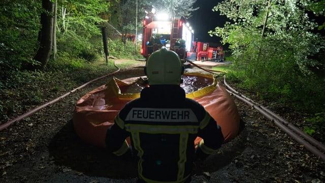 Feuerwehrmann vor Wasserbecken im Wald bei Nacht.