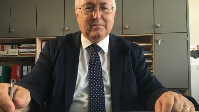 Jonas Motschi sitzt am Schreibtisch und hat vor sich das Sexarbeits-Gesetz.