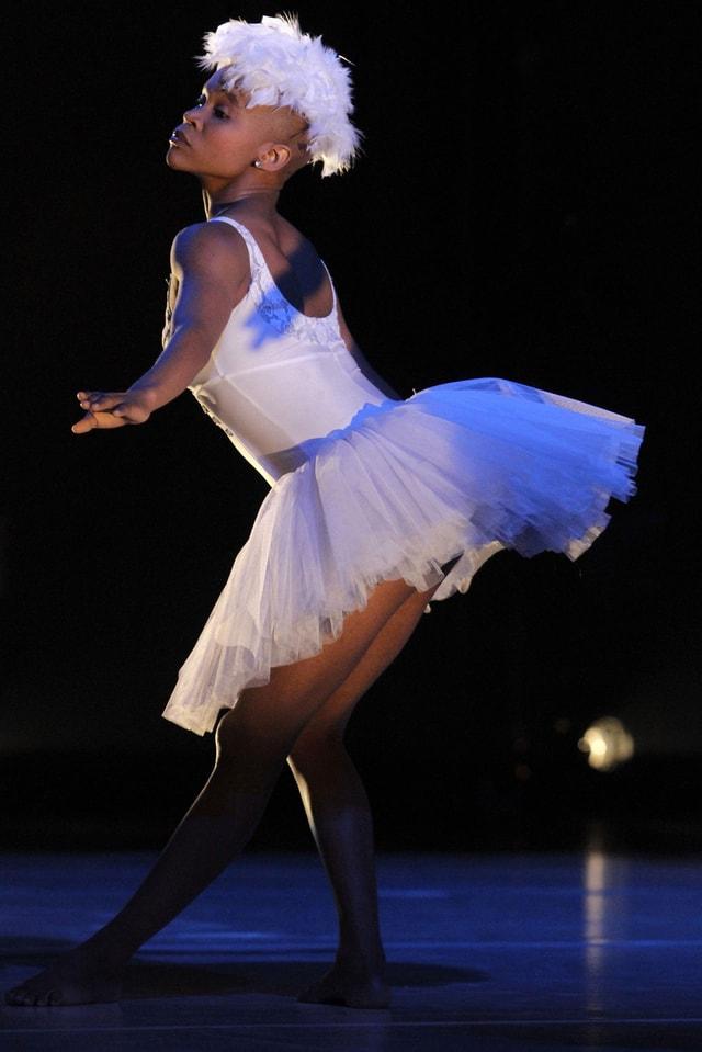 Die Tänzerin Dada Masilo, tanzend in einem weissen Tutu, mit weissen Federn auf dem Kopf.