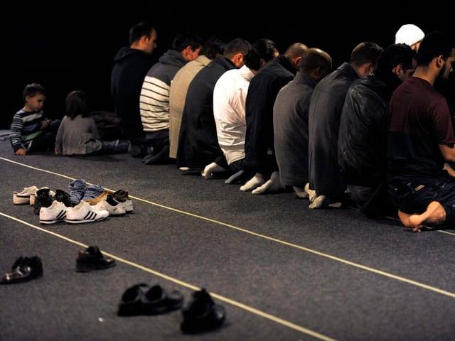 Männer am Boden am Beten, daneben Schuhe