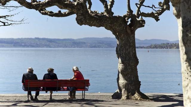 Senioren sitzen in Rapperswil-Jona (SG) am Ufer des Zürichsees auf einer Bank. (Keystone)