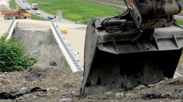 Eine Baggerschaufel im Vordergrund, im Hintergrund eine Baustelle.