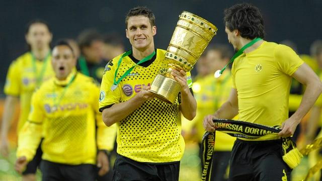 Dortmunds ehemaliger Captain Sebastian Kehl hält den DFB-Trophäe in den Händen und marschiert mit seinen Teamkollegen in die Fankurve.