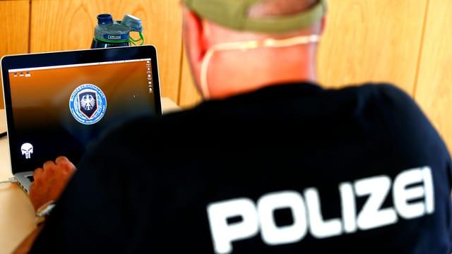 Ein Polizeibeamter von hinten. Er trägt ein schwarzes T-Shirt mit der Aufschrift Polizei. Er sitzt vor einem Computerbildschirm, auf dem das Signet des Deutschen Bundeskriminalamtes BKA zu sehen ist.