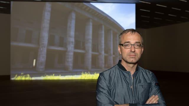 Man sieht den Künstler und ein Bild des Berliner Olympiastadions.