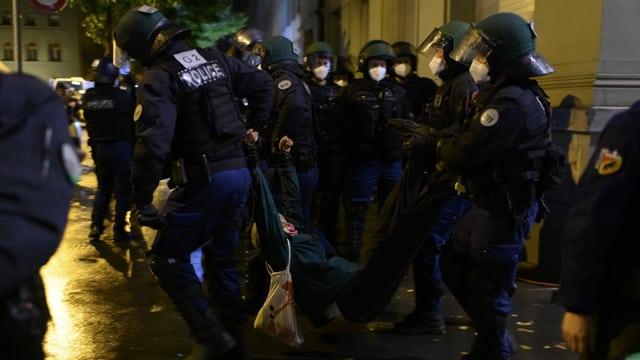 Polizisten tragen eine Aktivistin weg