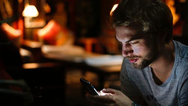 Mann blickt in dunklem Wohnzimmer auf sein Smartphone.