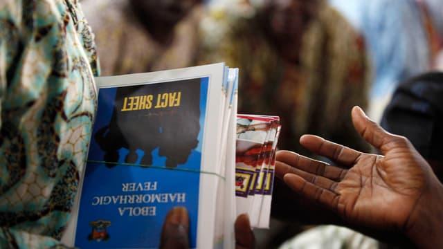 Eine Frau hält ein Faktenblatt zu Ebola in den Händen, ein Mann richtet seine offene Hand Richtung Blatt.