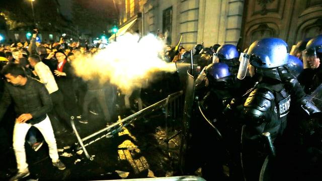 Französische Polizisten versprühen anlässlich der Präsidentschaftswahlen in Rumänien Tränengas in eine aufgebrachte Menge von Demonstranten, in Paris vor der rumänischen Botschaft.