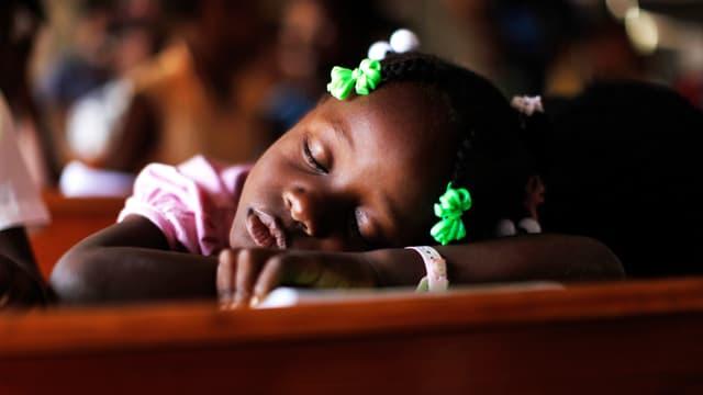 Ein schwarzes Mädchen schläft auf dem Schulpult.