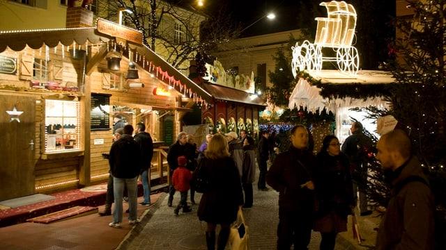 Beleuchtete Stände auf Weihnachtsmarkt in Basel, viele Besucher
