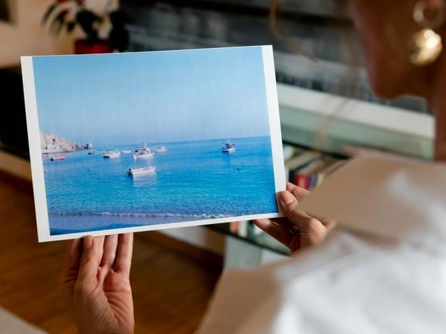 Eine Frau betrachtet ein Bild mit Meer und Schiffen.