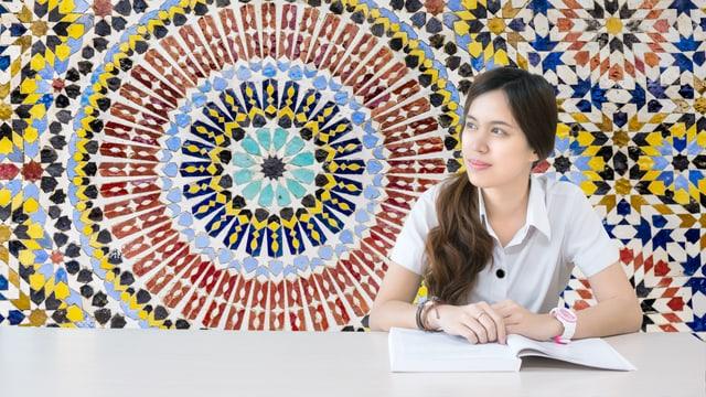 Eine Frau sitzt mit einem Buch an einem Tisch. Im Hintergrund ein islamisch anmutendes Mosaik.