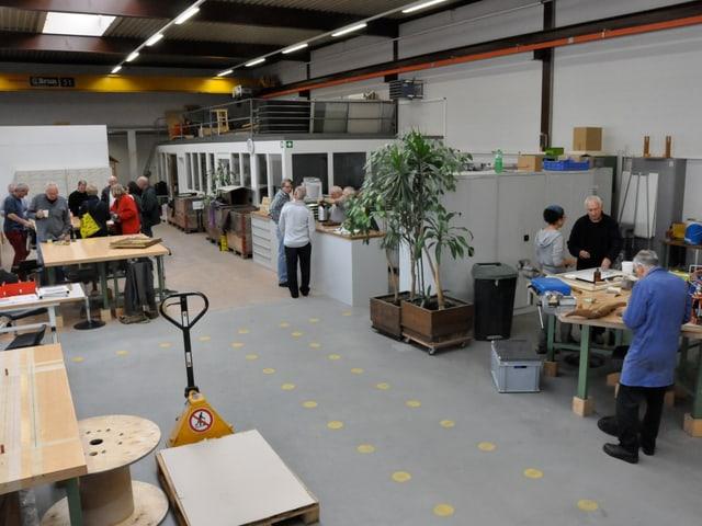 Eine Fabrikhalle mit verschiedenen Reparaturtischen