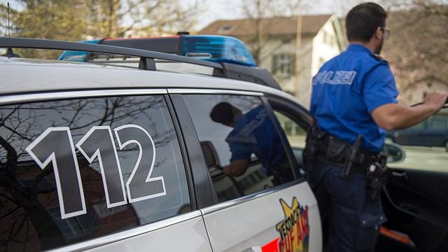 ein Polizist steigt ins Polizeiauto ein.