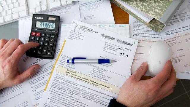 Hand, welche die Steuererklärung mithilfe eines Taschenrechners ausfüllt.