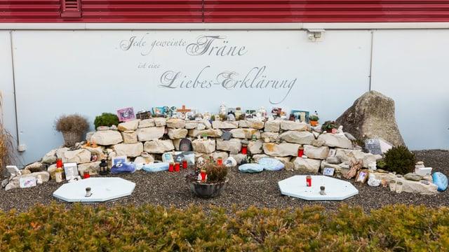 Gedenkstätte mit Kerzen und Steinen