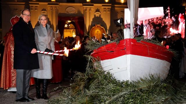 Fürst Albert und Fürstin Charlène zünden ein Boot an.