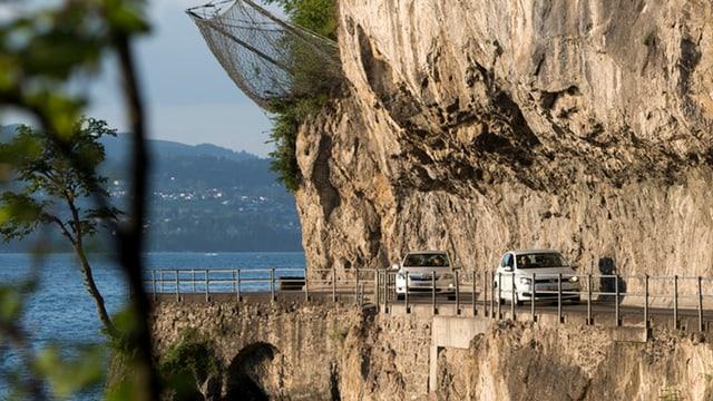Eine in den Fels gehauene enge Strasse an einem See - zwei weisse Autos fahren darauf.