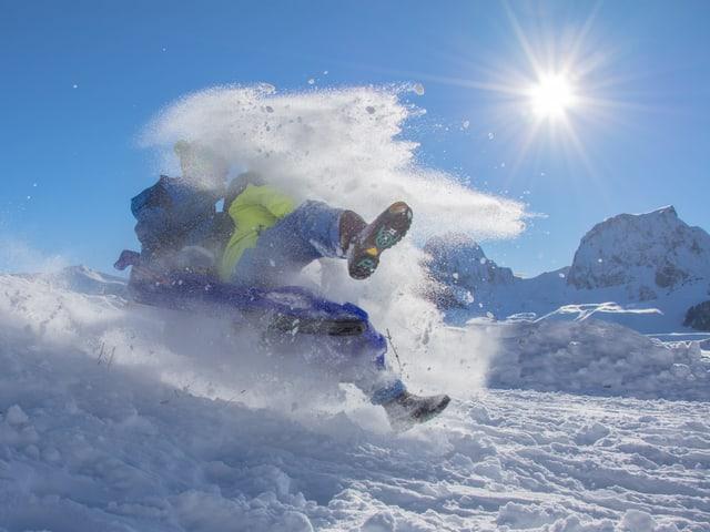 2 Personen auf Schlitte und Schneegestäube bei Sonnenschein