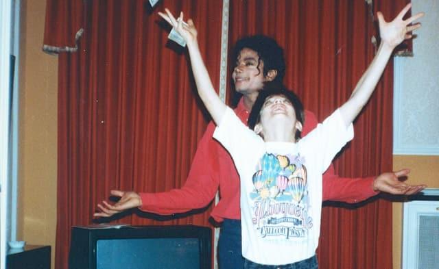 Michael Jackson steht hinter einem Jungen, der Geldscheine zu werfen oder zu fangen scheint. Die beiden lachen.