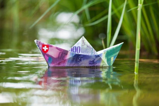 Ein zu einem Schiffchen gefaltete 100 Franken Note in einem Teich
