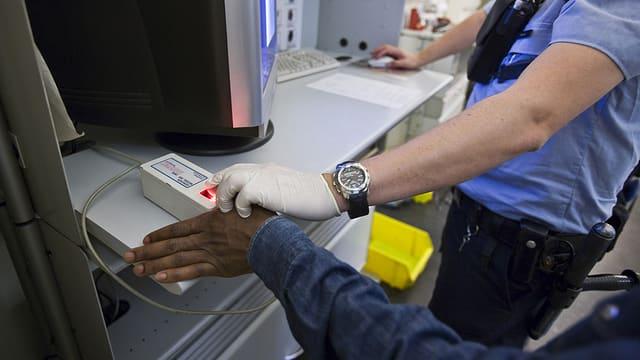 Polizist in Zürich nimmt von einem Mann Fingerabrücke.