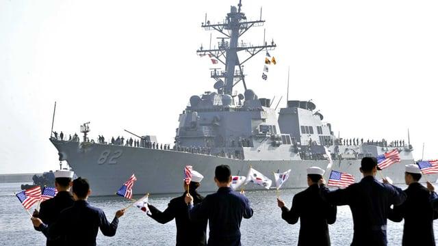 Südkoreanische Marine-Soldaten begrüssen ein US-Kriegsschiff am Hafen in Donghae. Sie schwenken südkoreanische und US-Flaggen.