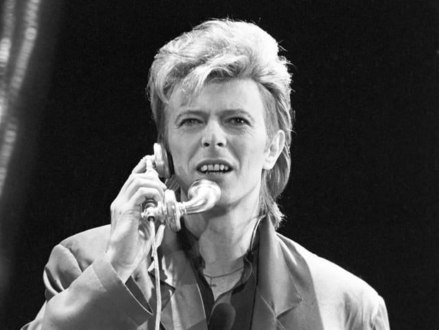David Bowie telefoniert auf der Bühne.