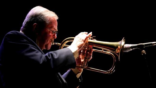 Kenny Wheeler, im Anzug, Trompete spielend, Blick von der Seite.