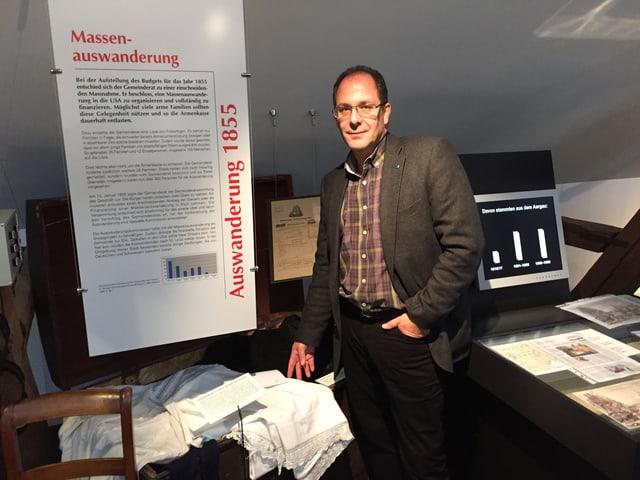 Adrian Schmitter steht neben einem Plakat, auf dem die Massenauswanderung beschrieben wird.