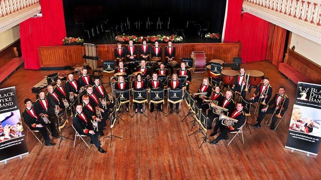 Das gesamte Orchester der Black Dyke Band in schwarz-rot-weiss.