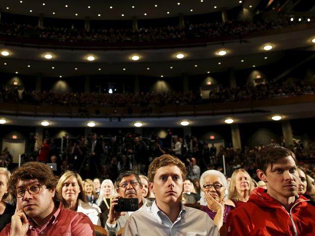 Zuschauer in einem Saal, im Vodergrund drei junge, weisse Männer.