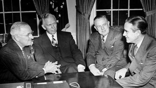 Vier Politiker an einem Schreibtisch