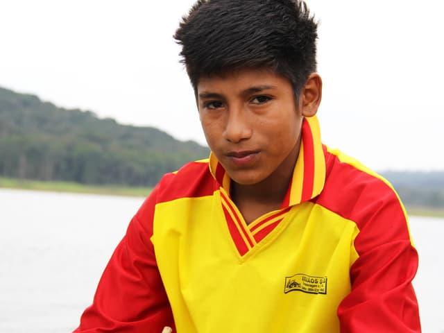 Werá Jeguaká Mirim im Porträt. Er trägt einen gelb-roten Pullover.