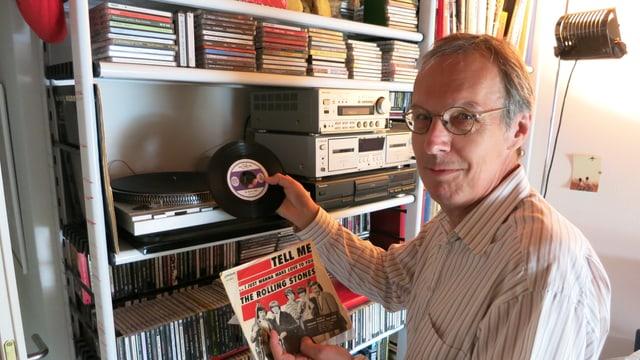 Ein Mann nimmt eine kleine Schallplatte auf einem Gestell.