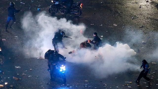 Tränengasschwaden. Polizisten und Demonstranten.