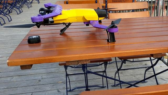 Das Bild zeigt die gelb-violette Airdog-Drohne (Quardocopter) auf einem Tisch des Bergrestaurants Tschentenalp.