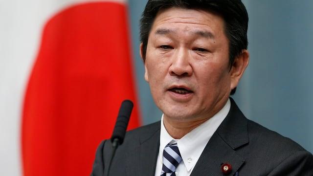 Toshimitsu Motegi am Rednerpult, dahinter eine Japan-Flagge.