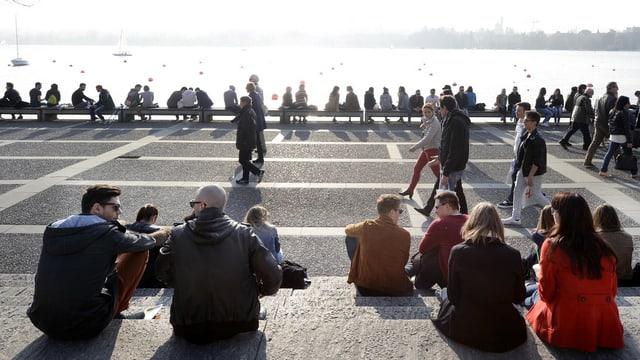Viele Menschen sitzen auf den Steintreppen am Ufer des Zürichsees an einem sonnigen Spätwinter-Tag.
