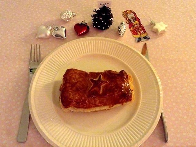 Blätzli im Butter-Blätterteig auf einem Papteller, Besteck und Weihnachtsdekoration.