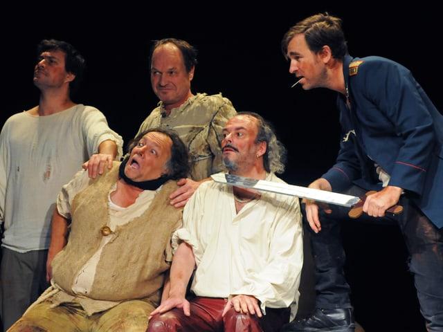 Fünf Personen, eine mit einem Schwert, schauen zur Seite.