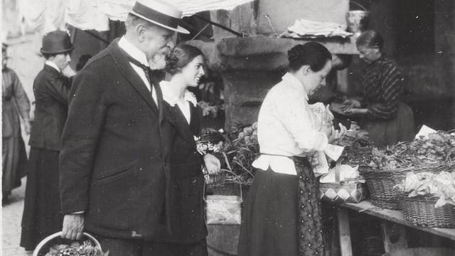 Ein älterer mann mit Hut beim Einkaufen auf einem Markt.