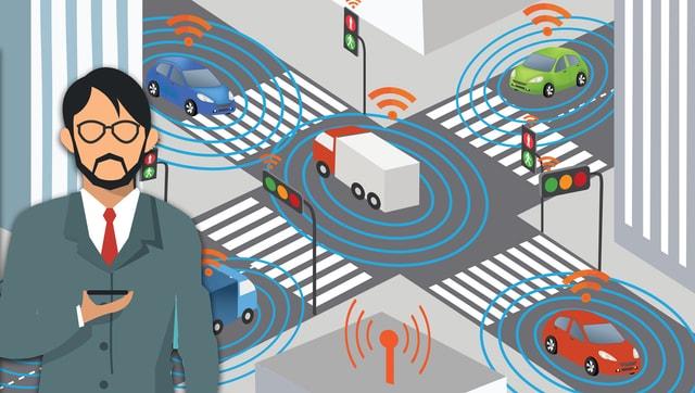 Grafik einer Kreuzung: alles Autos sind verbunden; im Vordergrund ein Mann mit Smartphone