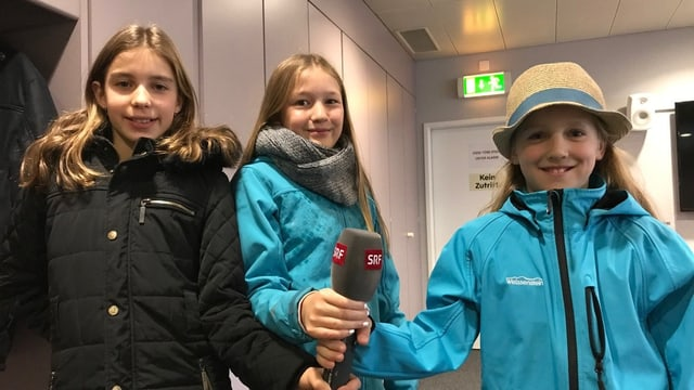 Drei Mädchen halten ein Mikrofon.