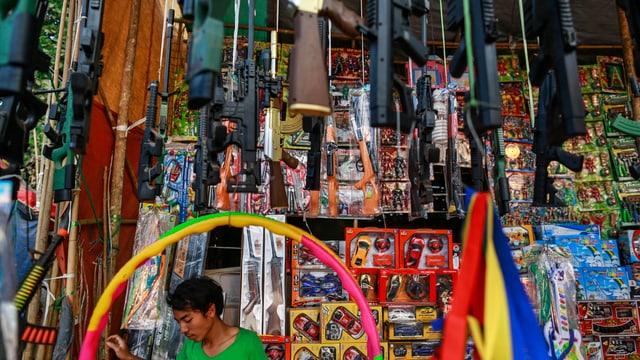 Ein Mann verkauft in einem Township nahe Yangon Spielzeug, aber auch Waffen.