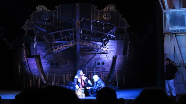 Imposantes Schiff, davor zwei Operndarsteller auf den Knien