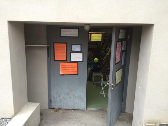 Eingang zu einem Gebäude, Tür steht offen, Plakate an der Wand.